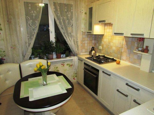 На фото уютный интерьер малогабаритной кухни гостиной с угловым диваном и круглым столом