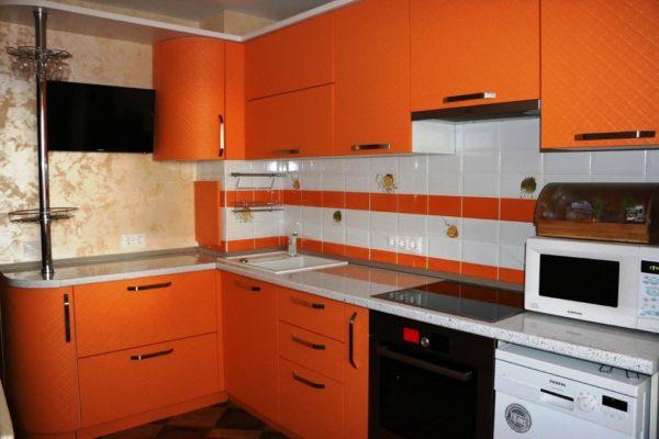 Пользуется популярностью фартук в виде кирпичной кладки, его можно выполнить из белой плитки, если гарнитур выбран апельсиновый