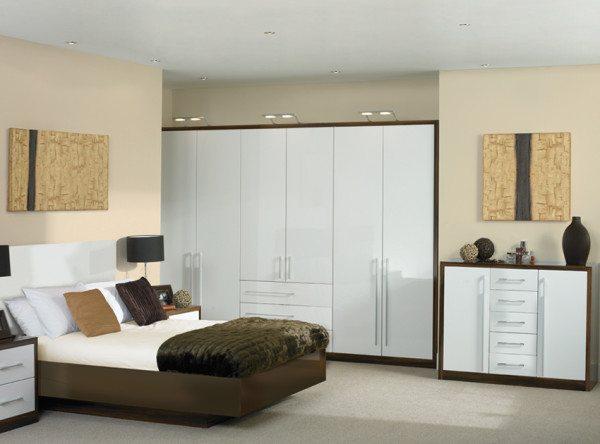 Белая глянцевая мебель для спальни в контрасте с графическими линиями по контуру темного дерева.