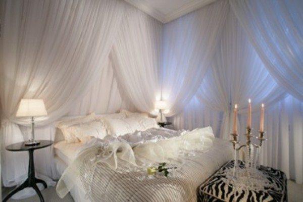 Белая спальня для молодоженов, в которой стены задрапированы легкой тканью.