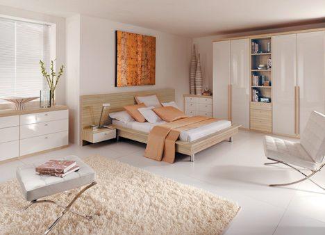 Белоснежный глянец мебели и пола удачно «разбавлен» ковром на полу и кроватью светлого дерева.