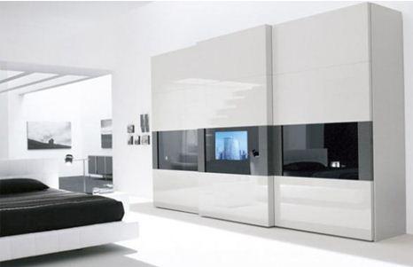 Белые глянцевые шкафы для спальни со встроенным телевизором в стиле хай-тек.
