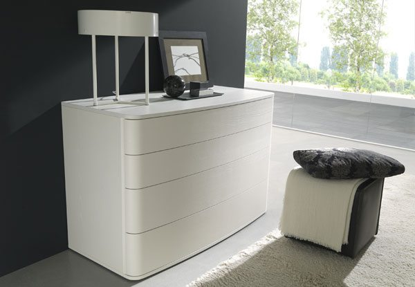 Белый комод в спальню в стиле модерн привлекателен плавностью линий и гармоничностью сочетания со светлой кроватью.