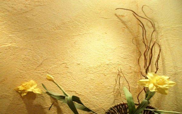 Фото грубо отделанной стены декоративной штукатуркой в светло-желтом тоне.