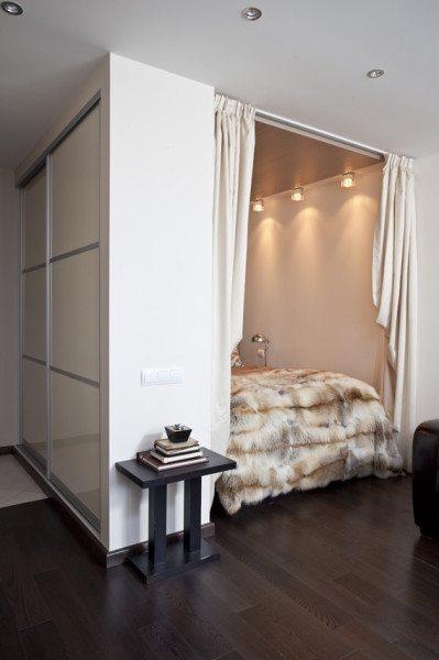 Фото комнаты в стиле минимализм, где спальное место отгорожено от гостиной с помощью ниши с плотными занавесями.