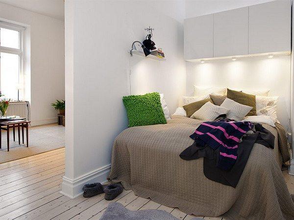 Фото спальни исключительно в белых тонах, в которой яркие элементы и текстиль в теплых тонах оживили атмосферу.