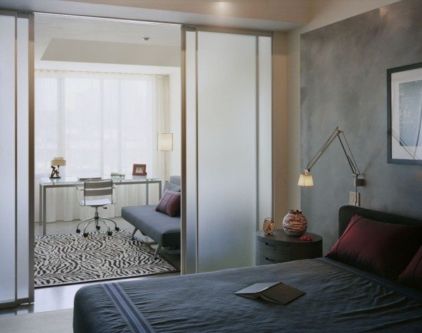 Фото спальни-кабинета, которая поделена с помощью стеклянной перегородки.