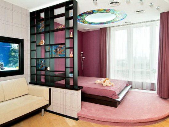 Фото спальни, совмещенной с гостиной, которая разграничена при помощи уровня пола и стеллажей.