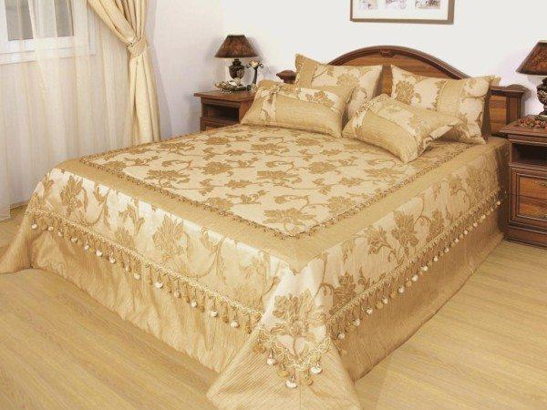 Гармоничный дизайн: атласное покрывало с такими же декоративными наволочками в тон штор.