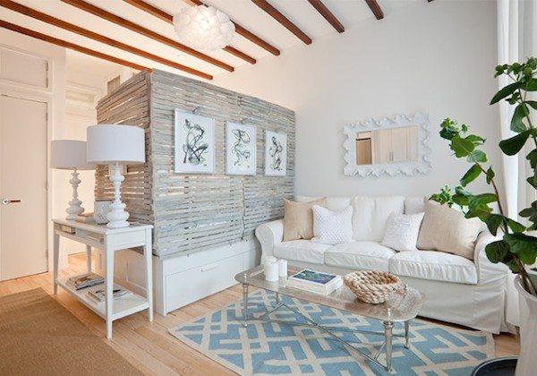 Гостиная со спальной зоной, где разграничение производилось при помощи плетеной перегородки, установленной на конструкции с ящиками.