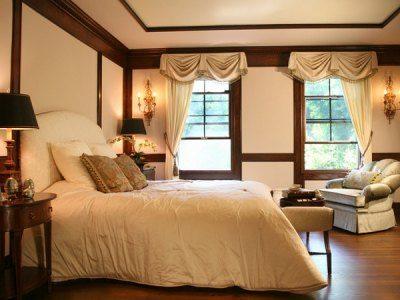 Коричневый потолок в спальне будет создавать гнетущее ощущение, а вот балки или карнизы в этом цвете смотрятся достойно