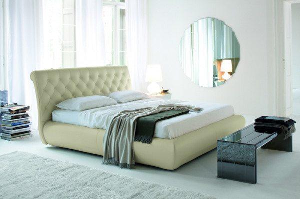 Кровать с высоким изголовьем около окна