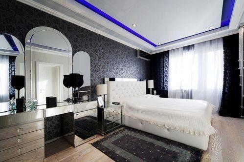 На фото изображена темная комната с белым ложе.