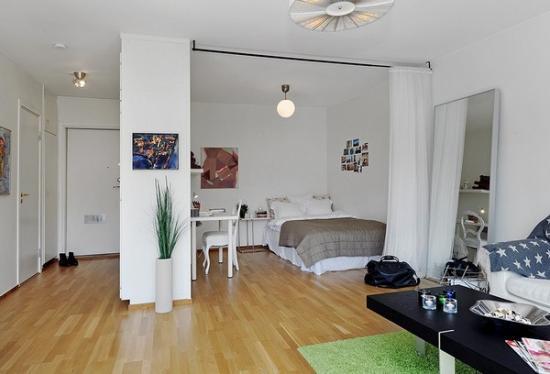 На фото комната разграничена на гостиную и спальное место при помощи обычной занавеси.