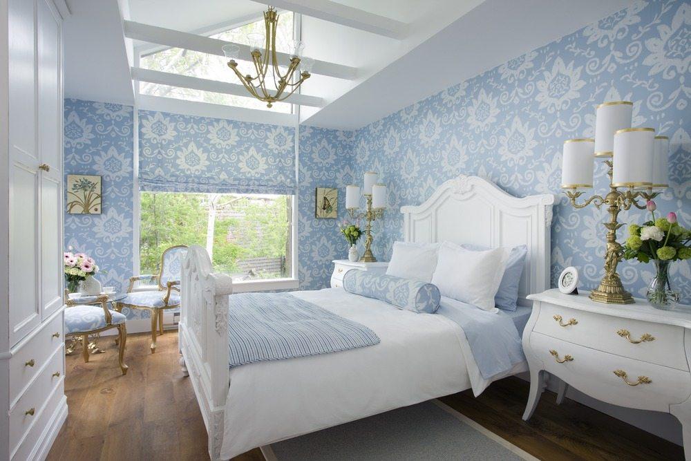 На фото мы видим голубой интерьер спальни, который сформирован за счет оформления стен и использования голубого текстиля.