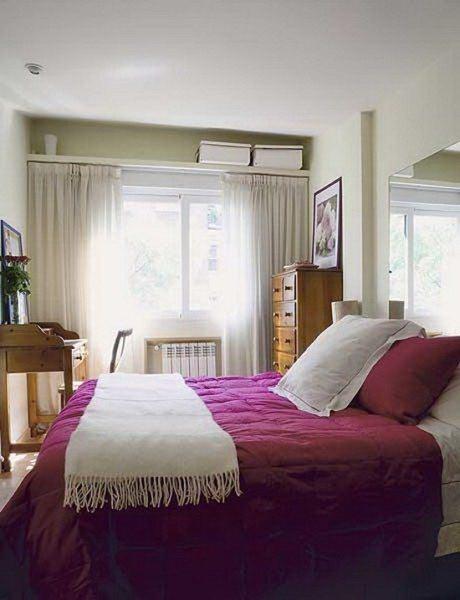 На фото показан вариант применения в маленькой спальне легких штор пастельных тонов.
