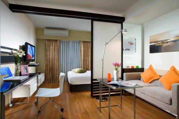 На фото показано разделение пространства жилой комнаты на рабочее место и зону отдыха при помощи раздвижной перегородки со стеклянными панелями.