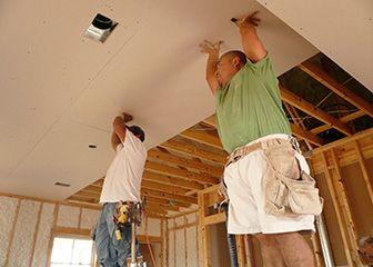 человек держит двумя руками гипсокартон на потолке