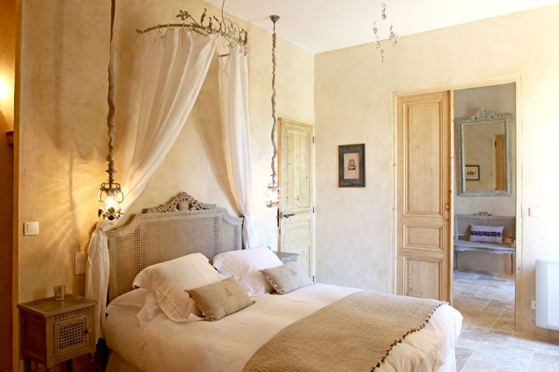 Основной элемент спальни – кровать – с более ажурной деревянной спинкой и балдахином на карнизе с кованными элементами.