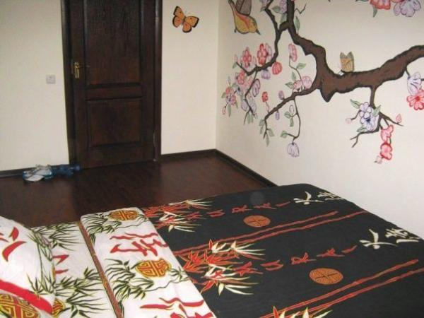 Роспись стены спальни гармонично смотрится совместно с покрывалом в японском стиле.