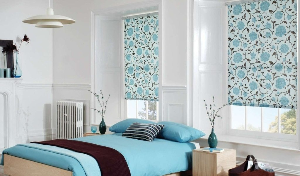 Рулонные шторы для голубой спальнис растительным рисунком прекрасно дополняют общее решение.