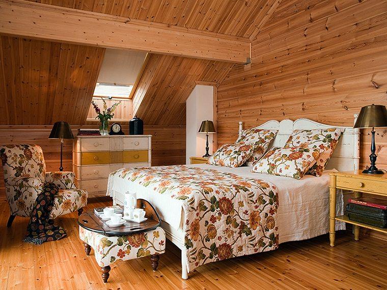 Спальня в мансарде деревянного коттеджа