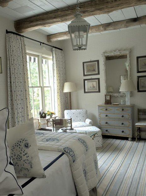 Спальня в стиле прованс с большим окном (от пола до потолка) – вариант оформления в сдержанных пастельных тонах, выдержана обстановка сельского дома. Освещение – «под стиль» кованый фонарь.