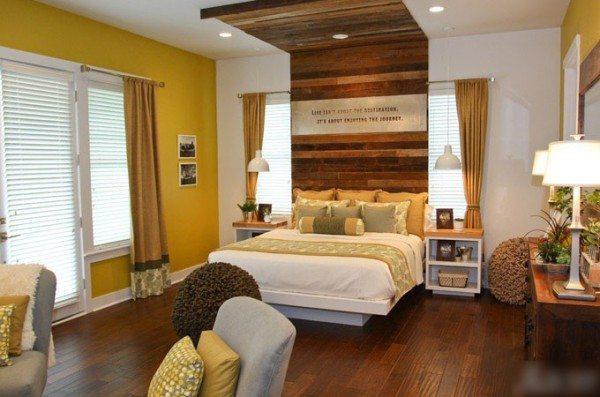 Спальня в теплых тонах. Необычное решение – вертикальная отделка, равная ширине кровати, в горизонтальную полоску – акцент на спальном месте.