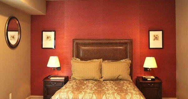 Стены комнаты в теплых насыщенных тонах, акцент у изголовья терракотового цвета.
