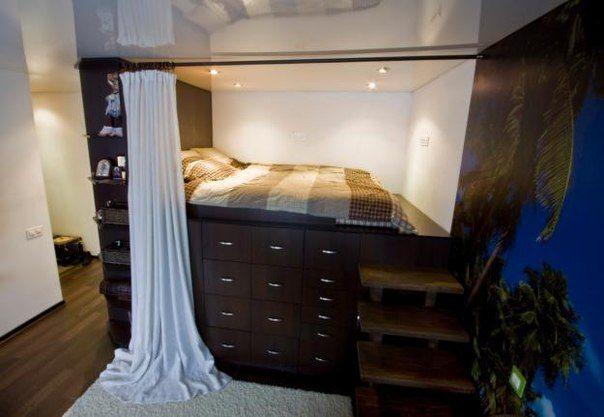 Удобная спальня в однокомнатной квартире получится, если вместо кровати в нише использовать высокий подиум с встроенными ящиками для хранения вещей.
