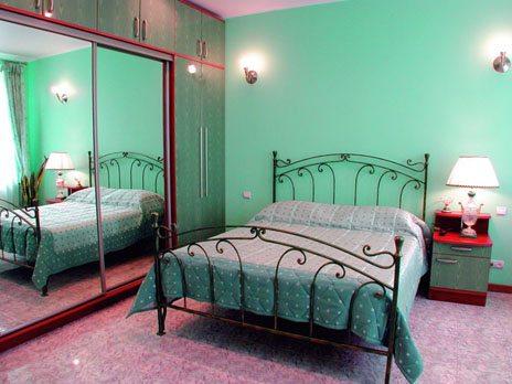 В спальне установлен шкаф-купе с зеркалами, имеется большая кровать.
