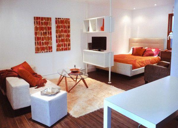 Вид спального места в комнате, разграниченной с использованием стеллажа.
