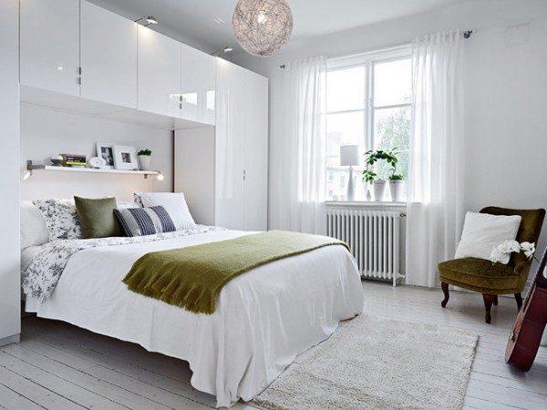 Живые комнатные цветы прекрасно дополняютдизайн спальни в белых тонах.